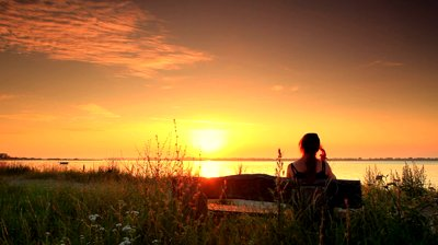 stock-footage-woman-sitting-on-a-bench-outside-looking-out-at-the-sea-at-sunset-in-copenhagen-denmark